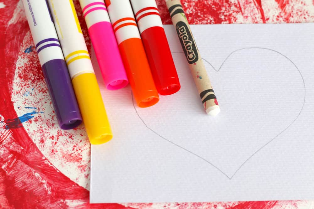 Markers, a white crayon and a piece of white paper with a heart drawn on it.