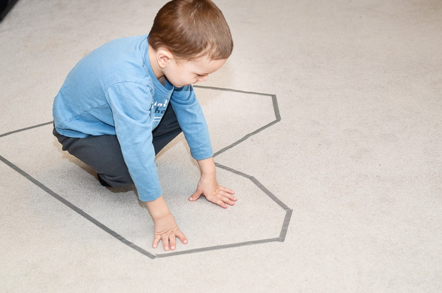 A child sits inside a heart made of tape on the floor.