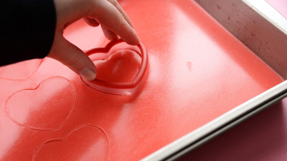 Cutting heart shapes from a tray of creamy red flavoured gelatin.