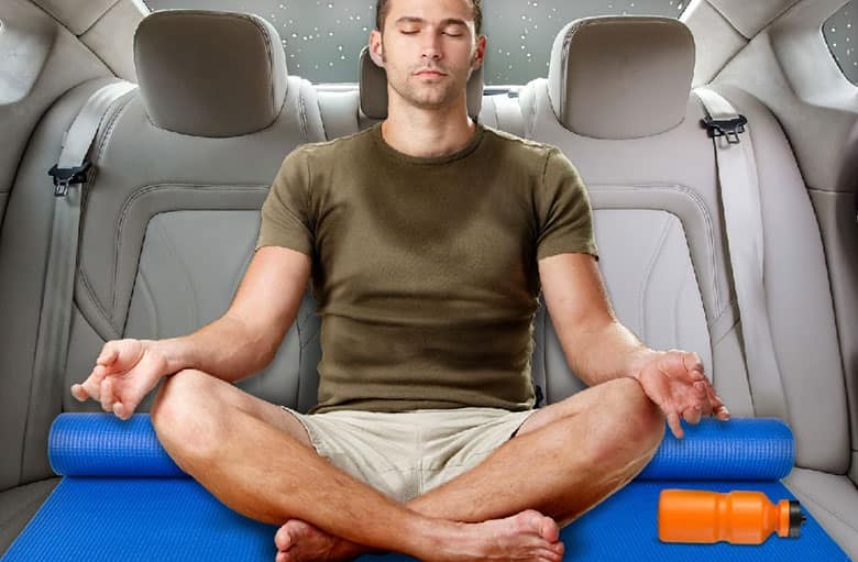 A stock photo collage of a man sitting on a yoga mat cross-legged in the backseat of a car.