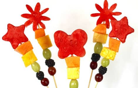 Rainbow-coloured fruits (blueberries, green grapes, pineapples, cantaloupe) threaded onto skewers with watermelon shapes at the top