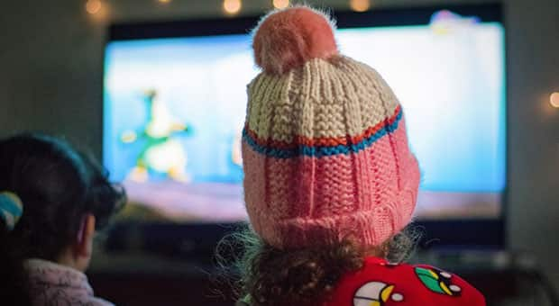 Two kids — one in a tuque — watching TV
