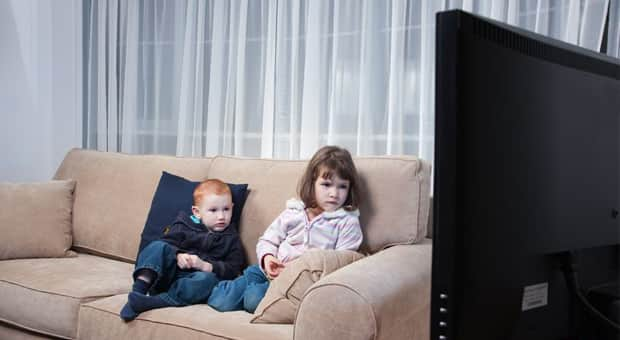 Two kids sitting on a couch watching TV.