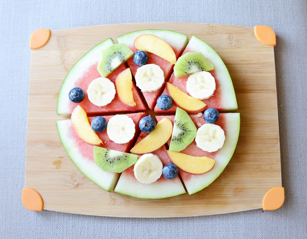 Fruits arranged on top of a round slice of watermelon to look like a pizza.