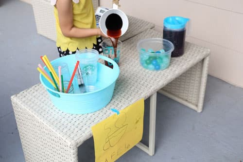 Pouring brown-coloured water into a cup.