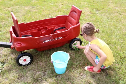 A little girl washing a wagon with a sponge and a bowl of soapy water.