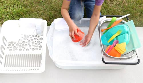 A tub of soapy water with plastic dishes being dipped and washed.