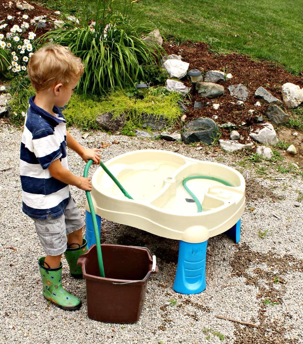 A boy uses a garden hose as a water siphon.