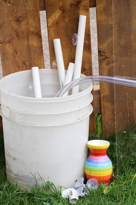 The supplies kids need to build on their water wall in a large bucket, sitting next to the fence.