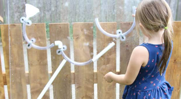 A little girl playing with a DIY water wall: a series of pipes and tubes on suction cups stuck to a big sheet of plexiglas.