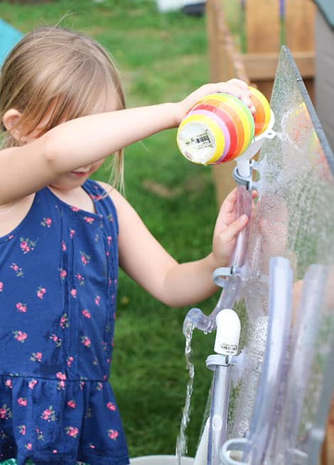 Little girl playing with the water wall by pouring water into a funnel and watching it flow out of a pipe.