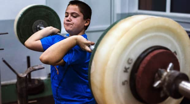 A young boy lifts heavy weight