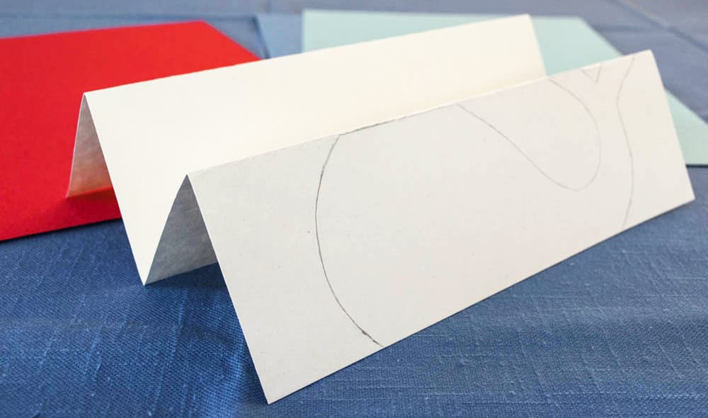 A piece of white paper with a whale traced onto it, folded in 4.