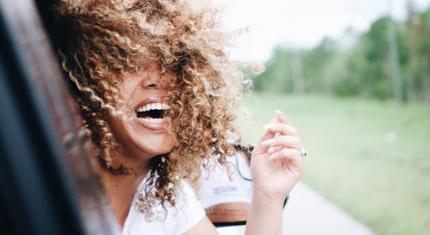 A woman with big curly hair is smiling big as she rides in a car along a quiet road