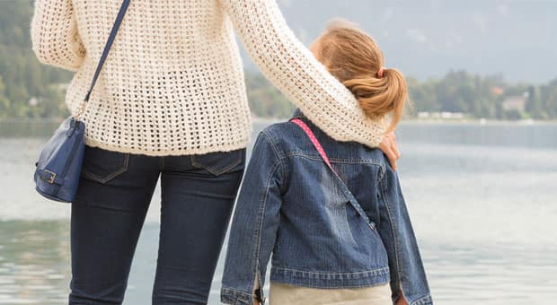 Viewed from behind, a mother with her arms around the shoulders of her young daughter.
