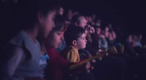 white kids watching a movie in a theatre