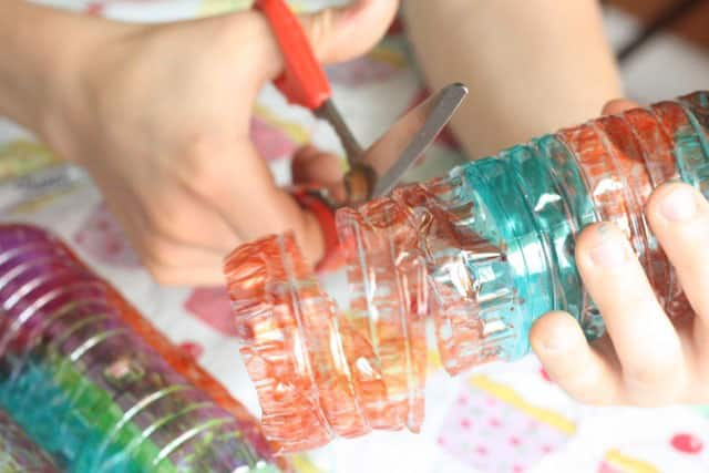 A child cutting a coloured water bottle.