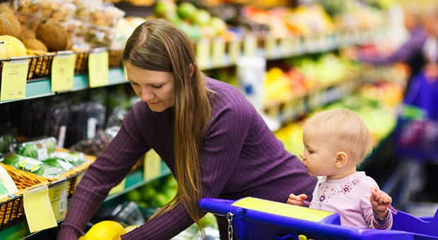 Woman picking out fresh produce with baby in cart