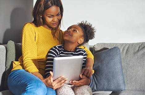 Woman reading iPad with daughter.