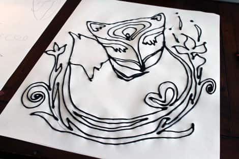 A sheet of paper with a black glue outline of a fox.