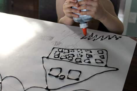 A child using black glue to sketch out a story.