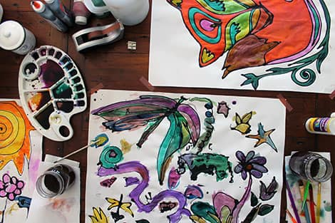 A table covered with paints and paper and art.