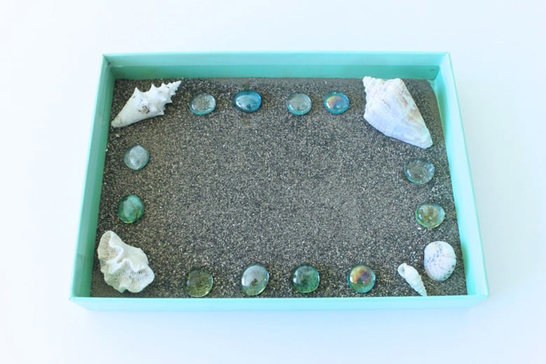A box filled with sand, shells and gems.