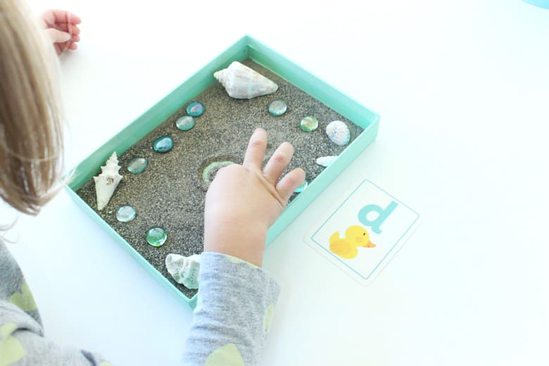 A child draws a letter d in a beach-themed writing tray.