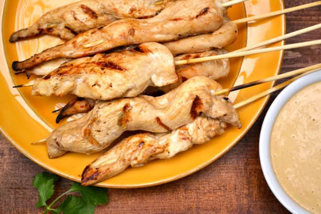 Skewers of grilled chicken satay piled on a plate next to a bowl of peanut sauce.