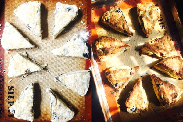 A baking sheet lined with a silpat with wedge-style blueberry scones.