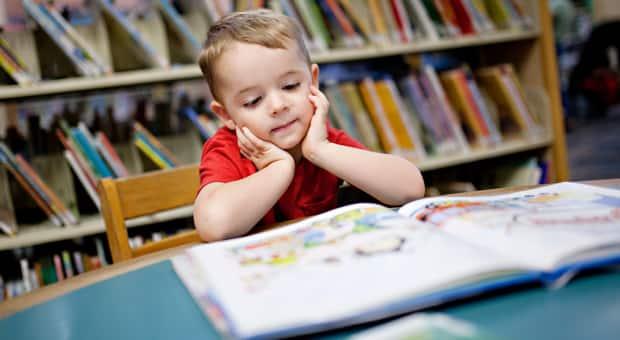 a young boy reads a book in a library