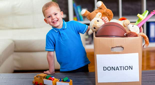 Little boy with donation box full of toys