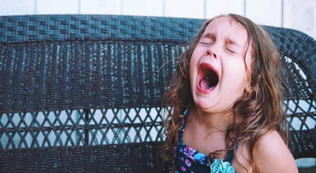A young girl is crying with her mouth wide open