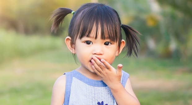 A young girl stands holding her hand to her mouth
