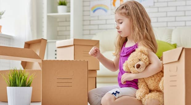 A young girl is packing her belongings in boxes