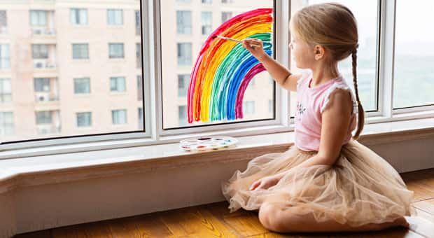 A young girl paints a rainbow on her window