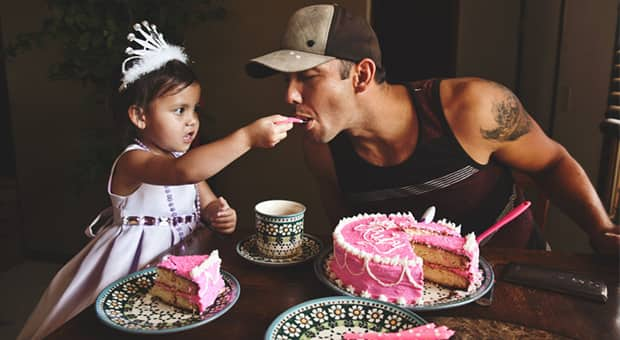 Dad eats cake from daughter's spoon