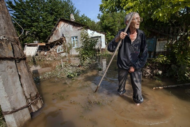 A local resident stands at a flooded house in Krimsk. Russian President Vladimir Putin ordered an inquiry into whether enough had been done to warn people about the floods.