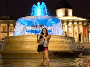 A lady poses in the fountains at Trafalgar Square which are lit blue