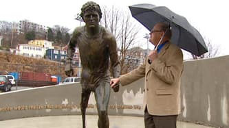 Rolly Fox holds the hand on a statue of his son, Terry Fox, soon after its unveiling in St. John's in 2012. (CBC )