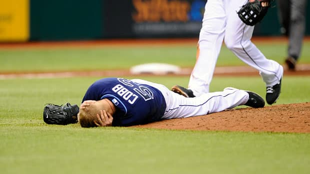 Tampa Bay Rays starting pitcher Alex Cobb grabs his head and lies on the pitcher's mound after being hit by a line drive during the fifth inning of a baseball game on Saturday in St. Petersburg, Fla. Cobb was taken off the field on a stretcher. (Brian Blanco/Associated Press)