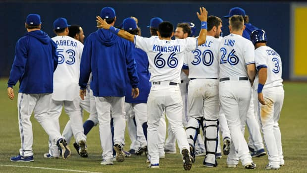 Munenori Kawasaki (66) was always quick to cheer on and congratulate his Blue Jays teammates, like here after a win against the Baltimore Orioles on Friday, the same game where he hit his first MLB home run. (Brad White/Getty Images)