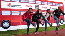 Perdita Felicien, left, Priscilla Lopes-Schliep, Nikkita Holder, and Phylicia George ham it up in front of a bus mural prior to the start of the Timex Track and Field Trials at Foothills Athletic Park in Calgary on Tuesday. (Jeff McIntosh/Canadian Press)