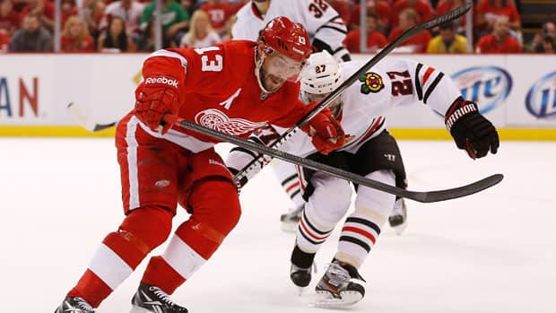Pavel Datsyuk, left, of the Detroit Red Wings looks to drive around Chicago Blackhawks defender Johnny Oduya during the first period in Game 3 at Joe Louis Arena on Monday in Detroit. (Gregory Shamus/Getty Images)