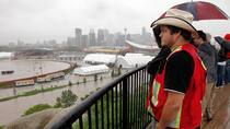 People look out over the flooded Calgary Stampede grounds and Saddledome due to the heavy rains in Calgary on Friday. (Jeff McIntosh/Canadian Press)