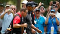 Tiger Woods and his swing coach Sean Foley stroll past a phalanx of camera-toting golf fans at Merion Golf Club on Tuesday. (Adam Hunger/Reuters)