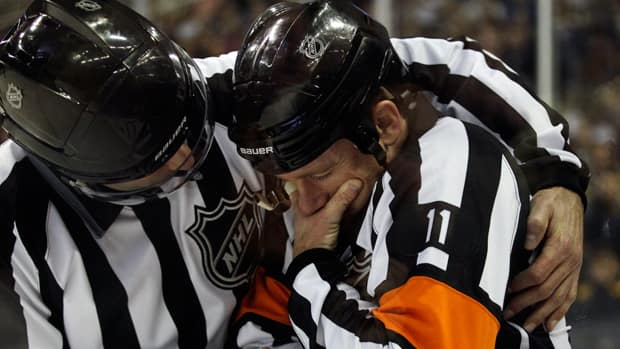 Referee Kelly Sutherland, right, is helped by linesman Steve Miller, left, after being injured during the first period in Buffalo, N.Y., on Wednesday. (David Duprey/Associated Press)