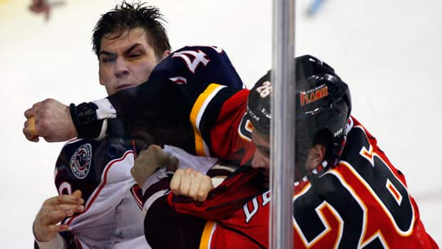 The Columbus Blue Jackets' Jared Boll, left, fights with Calgary Flames' Guillaume Desbiens during the first period in Calgary, Alta., on Sunday. (Jeff McIntosh/Canadian Press)