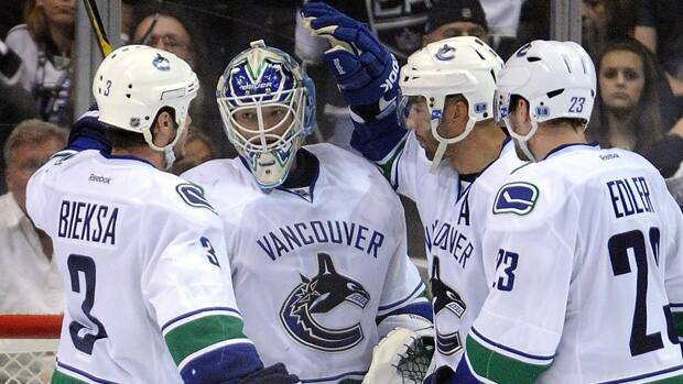 Cory Schneider, centre, of the Vancouver Canucks celebrates a 3-1 win over the Los Angeles Kings with Kevin Bieksa, Manny Malhotra and Alexander Edler on Wednesday. (Harry How/Getty Images)