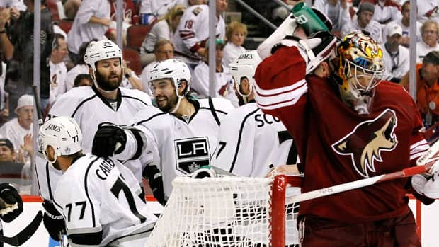 As Phoenix Coyotes goalie Mike Smith, far right, sprays water on his neck, Los Angeles Kings' Drew Doughty (8) celebrates with Rob Scuderi (7), Dustin Penner (25) and Jeff Carter (77) after a goal by Carter in the second period during Game 2 on Tuesday in Glendale, Ariz. (Ross D. Franklin/Associated Press)